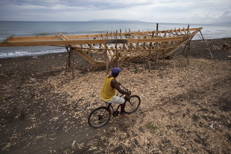 A bicyclist passes the frame of a sailboat under construction in Leogane, Haiti, on Saturday, May 4, 2013. The 30-foot-long boats, the frames of which resemble the rib cage of a small dinosaur, are purchased by smugglers for about $12,000 and then taken to northern Haiti to find passengers. (AP Photo/Dieu Nalio Chery)
