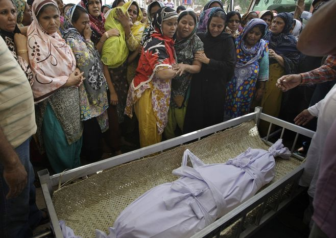 ** FILE ** Pakistani women mourn on Sunday, May 5, 2013, in Karachi, Pakistan, during the funeral of a child killed in a bombing on Saturday. The two blasts also killed two others near the office of a political party critical of the Taliban, heightening tensions ahead of the country's historic May 11 election. (AP Photo/Fareed Khan)
