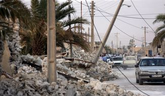 ** FILE ** Vehicles make their way along structures destroyed by an earthquake which struck southern Iran in the city of Shonbeh, Iran, Tuesday, April 9, 2013. (AP Photo/Fars News Agency, Mohammad Fatemi)