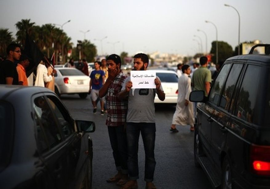 A Libyan follower of Ansar al-Sharia Brigades carries a sign during a protest in front of the Tibesti Hotel, in Benghazi. (Credit: Associated Press)