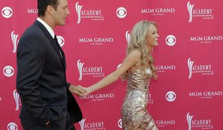 **FILE** Carrie Underwood, nominated for top female vocalist, guides boyfriend, Dallas Cowboys quarterback Tony Romo, along the red carpet as they arrive at the 42nd Annual Academy of Country Music Awards on Tuesday, May 15, 2007, in Las Vegas. (AP Photo/Jae C. Hong)