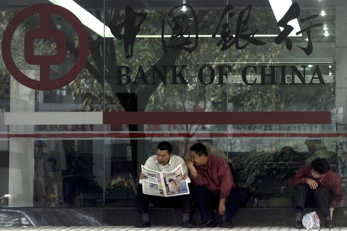 ** FILE ** In this photo taken Tuesday, Jan 6, 2004, Chinese men share a newspaper outside a Bank of China branch in Guangzhou, southeastern China Guangdong province. One of China's biggest banks said Tuesday, May 7, 2013, that it has halted business with the Foreign Trade Bank of North Korea. (AP Photo/Ng Han Guan)