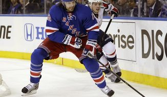 Washington Capitals defenseman John Carlson (74) pursues New York Rangers left wing Rick Nash (61) who controls the puck in the second period of Game 3 of their first-round NHL hockey Stanley Cup playoff series in New York, Monday, May 6, 2013. (AP Photo/kathy willens)