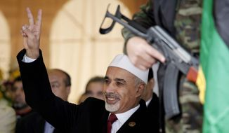** FILE ** In this Sunday, Feb. 17, 2013, file photo, Libyan interim president, Mohammed el-Megarif, flashes the victory sign to crowds during the celebration of the second anniversary of the Libyan revolution in Benghazi, Libya. Libya's parliament passed a law on Sunday, May 5, 2013, that bans officials who held senior positions under ousted dictator Moammar Gadhafi from holding high-level government posts. (AP Photo/Mohammad Hannon, File)