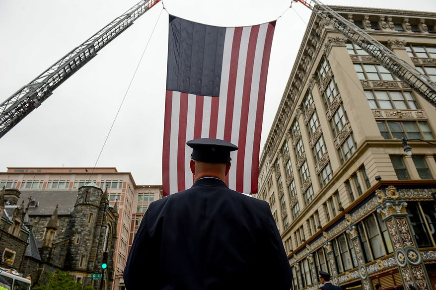 A Washington, D.C. Firefighter stands under a large American flag at the conclusion of Blue Mass at St. Patrick Catholic Church, Washington, D.C., Tuesday, May 7, 2013. The Blue Mass is held to pray for those in law enforcement and fire safety, remember those who have fallen, and support those who serve at the beginning of National Police Week.  (Andrew Harnik/The Washington Times)