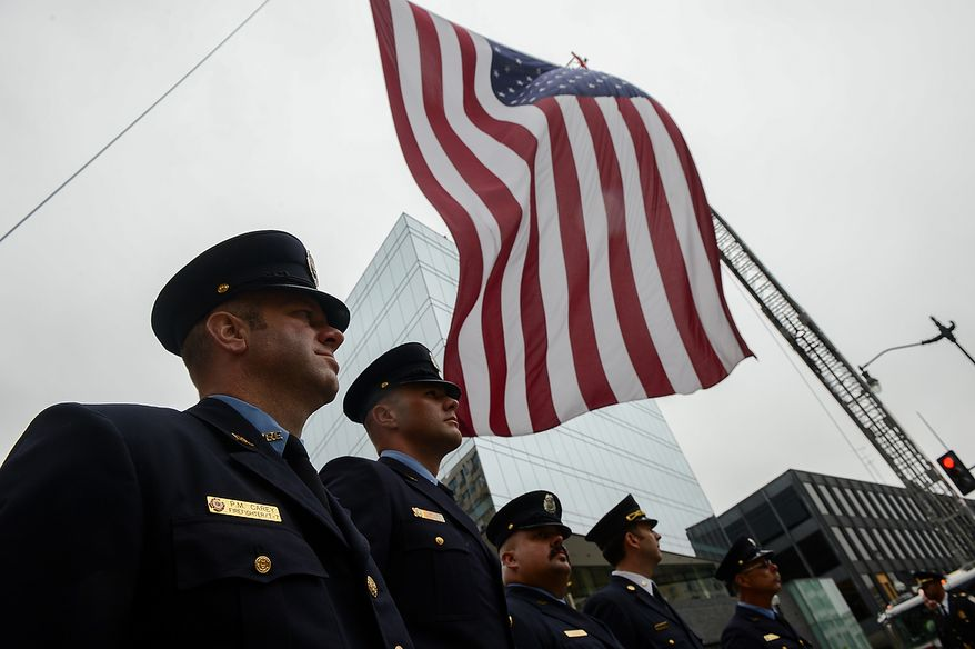 Washington, D.C. Firefighters stand at attention under a large American flag at the conclusion of Blue Mass at St. Patrick Catholic Church, Washington, D.C., Tuesday, May 7, 2013. The Blue Mass is held to pray for those in law enforcement and fire safety, remember those who have fallen, and support those who serve at the beginning of National Police Week.  (Andrew Harnik/The Washington Times)