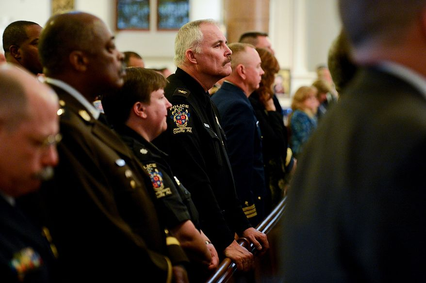 Montgomery County Police Chief J. Thomas Manger, center, listens as a police officer plays taps for officers who have died in the line of duty in 2012 during Blue Mass at St. Patrick Catholic Church, Washington, D.C., Tuesday, May 7, 2013. The Blue Mass is held to pray for those in law enforcement and fire safety, remember those who have fallen, and support those who serve at the beginning of National Police Week.  (Andrew Harnik/The Washington Times)