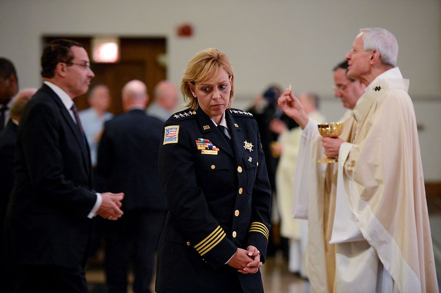 Washington, D.C. Mayor Vincent Gray, left, and Washington, D.C. Metropolitan Police Chief Cathy Lanier, center, take communion from Cardinal Donald Wuerl, Archbishop of Washington, right, during Blue Mass at St. Patrick Catholic Church, Washington, D.C., Tuesday, May 7, 2013. The Blue Mass is held to pray for those in law enforcement and fire safety, remember those who have fallen, and support those who serve at the beginning of National Police Week.  (Andrew Harnik/The Washington Times)