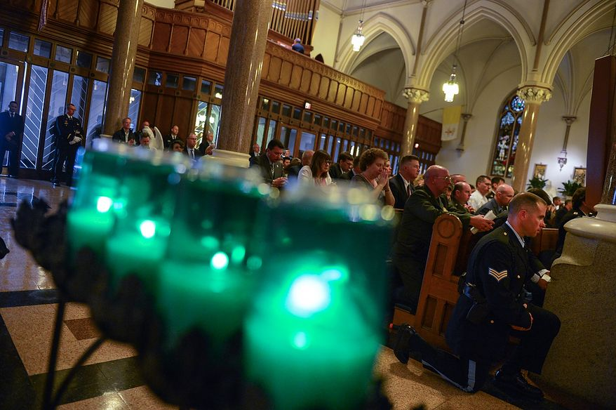 U.S. Park Police Sgt. J. Jarboe, right, kneels in the isle during Blue Mass at St. Patrick Catholic Church, Washington, D.C., Tuesday, May 7, 2013. The Blue Mass is held to pray for those in law enforcement and fire safety, remember those who have fallen, and support those who serve at the beginning of National Police Week.  (Andrew Harnik/The Washington Times)