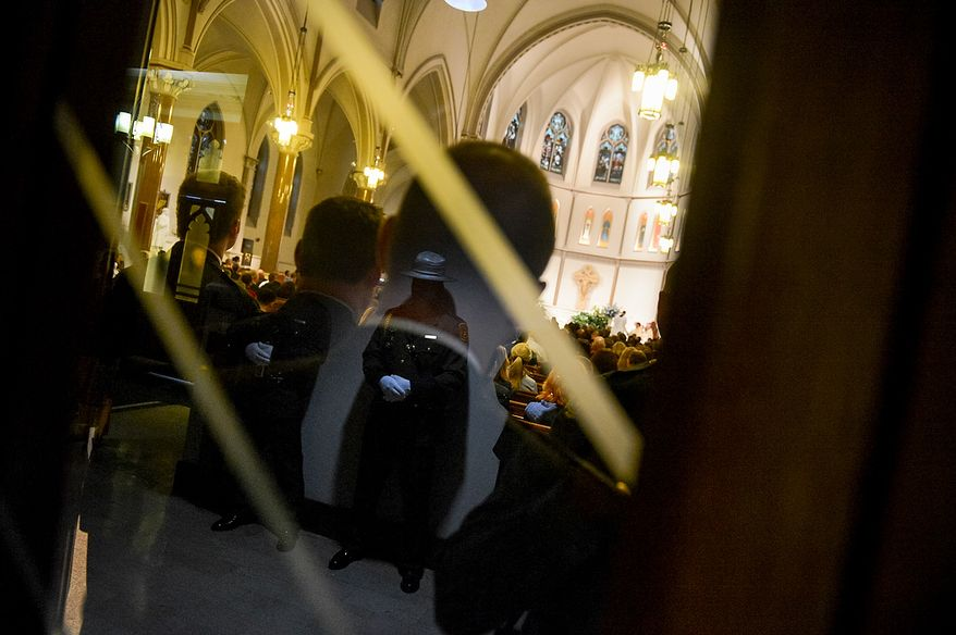 Officers stands at attention during Blue Mass in the lobby of St. Patrick Catholic Church, Washington, D.C., Tuesday, May 7, 2013. The Blue Mass is held to pray for those in law enforcement and fire safety, remember those who have fallen, and support those who serve at the beginning of National Police Week.  (Andrew Harnik/The Washington Times)