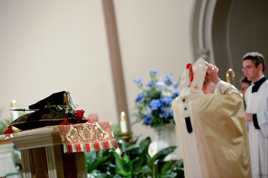 A rose and an officer's hat are placed at a lectern as Cardinal Donald Wuerl, Archbishop of Washington, second from right, arrives at the start of the annual Blue Mass held at St. Patrick Catholic Church, Washington, D.C., Tuesday, May 7, 2013. The Blue Mass is held to pray for those in law enforcement and fire safety, remember those who have fallen, and support those who serve at the beginning of National Police Week.  (Andrew Harnik/The Washington Times)
