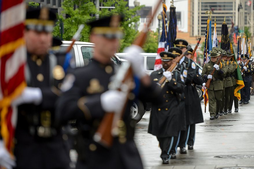 Units from federal, state, and local jurisdictions march in formation under a huge American flag hung between two fire ladder trucks before the start of the annual Blue Mass held at St. Patrick Catholic Church, Washington, D.C., Tuesday, May 7, 2013. The Blue Mass is held to pray for those in law enforcement and fire safety, remember those who have fallen, and support those who serve at the beginning of National Police Week.  (Andrew Harnik/The Washington Times)