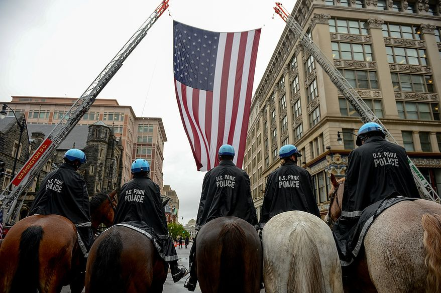 ** FILE ** U.S. Park Police officers on horseback line up to watch units from federal, state, and local jurisdictions march in formation under a huge American flag hung between two fire ladder trucks before the start of the annual Blue Mass held at St. Patrick Catholic Church, Washington, D.C., Tuesday, May 7, 2013. The Blue Mass is held to pray for those in law enforcement and fire safety, remember those who have fallen, and support those who serve at the beginning of National Police Week.  (Andrew Harnik/The Washington Times)