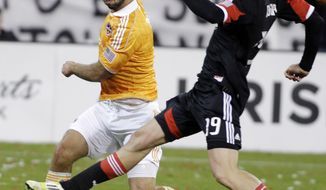 **FILE** Houston Dynamo's Will Bruin, left, kicks the ball as D.C. United's Emiliano Dudar (19) defends during the second half of the second game of an MLS soccer Eastern Conference final playoff series, Sunday, Nov. 18, 2012, in Washington. The Dynamo advanced to their second straight MLS Cup final and fourth in seven years, tying D.C. United 1-1 Sunday for a 4-2 aggregate win in the Eastern Conference final. (AP Photo/Luis M. Alvarez)