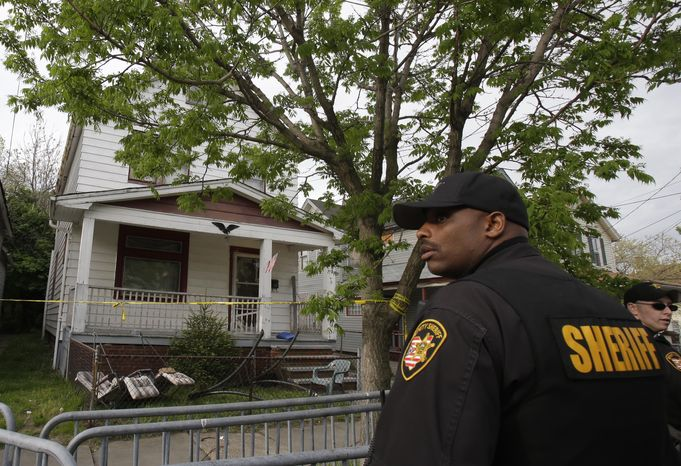 On Tuesday, May 7, 2013, a sheriff's deputy stands outside a Cleveland house from which three women escaped on Monday after being held in captivity for about a decade, police said. (AP Photo/Tony Dejak)