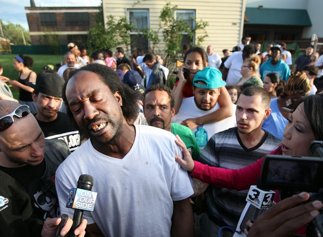 Neighbor Charles Ramsey speaks to the media on Monday, May 6, 2013, near the home on the 2200 block of Seymour Avenue in Cleveland where three missing women were rescued. (AP Photo/The Cleveland Plain Dealer, Scott Shaw)