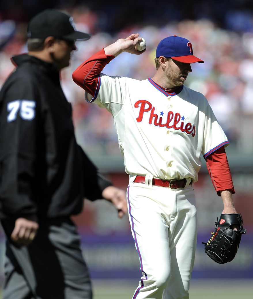 Philadelphia Phillies' Roy Halladay, right, steps off the mound as third base umpire Chad Fairchild walks over to review a home run by Miami Marlins' Adeiny Hechavarria in the third inning of a baseball game on Sunday, May 5, 2013, in Philadelphia. (AP Photo/Michael Perez)