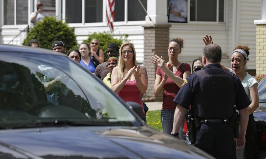 """Neighbors and friends of Amanda Berry clap as she arrives at her sister's home in Cleveland on Wednesday, May 8, 2013. Ms. Berry, 27, Michelle Knight, 32, and Georgina """"Gina"""" DeJesus, 23, apparently were held captive for a decade, police said. (AP Photo/Tony Dejak)"""