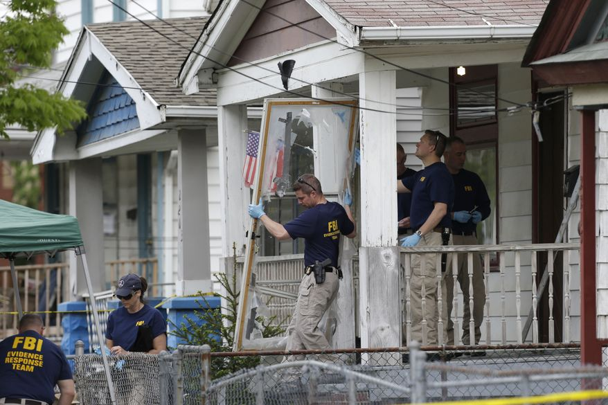 ** FILE ** On Tuesday, May 7, 2013, members of an FBI evidence response team carry out the front screen door from a house in Cleveland where three women were held against their will for a decade. (AP Photo/Tony Dejak)