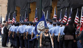**FILE** Philadelphia police officers go inside as a woman carries a U.S. Navy flag, at services for U.S.Navy Petty Officer 1st Class Michael Joseph Strange, a cryptology technician, at the Cathedral Basilica of Saints Peter and Paul, on Aug. 18, 2011, in Philadelphia. Strange was assigned to the Navy SEAL team whose Chinook helicopter was shot down Aug. 6 by a rocket-propelled grenade in what has become the deadliest single loss for U.S. forces in the decade-long war in Afghanistan. (Associated Press)