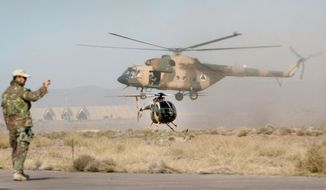 **FILE** A U.S. donated helicopter flies around after it was donated to Afghan air force in Shindand district of Herat province, west of Kabul, Afghanistan, on Dec. 10, 2011. (Associated Press)