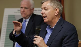 **FILE** Sen. Lindsey Graham, South Carolina Republican, speaks as Sen. John McCain, Arizona Republican, listens during a town hall meeting on April 29, 2013, in Goodyear, Ariz. McCain and Graham were speaking and taking questions on immigration and sequestration. (Associated Press)
