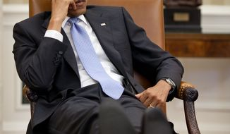 President Obama takes a down moment in the Oval Office with his feet up. (Credit: Pete Souza)