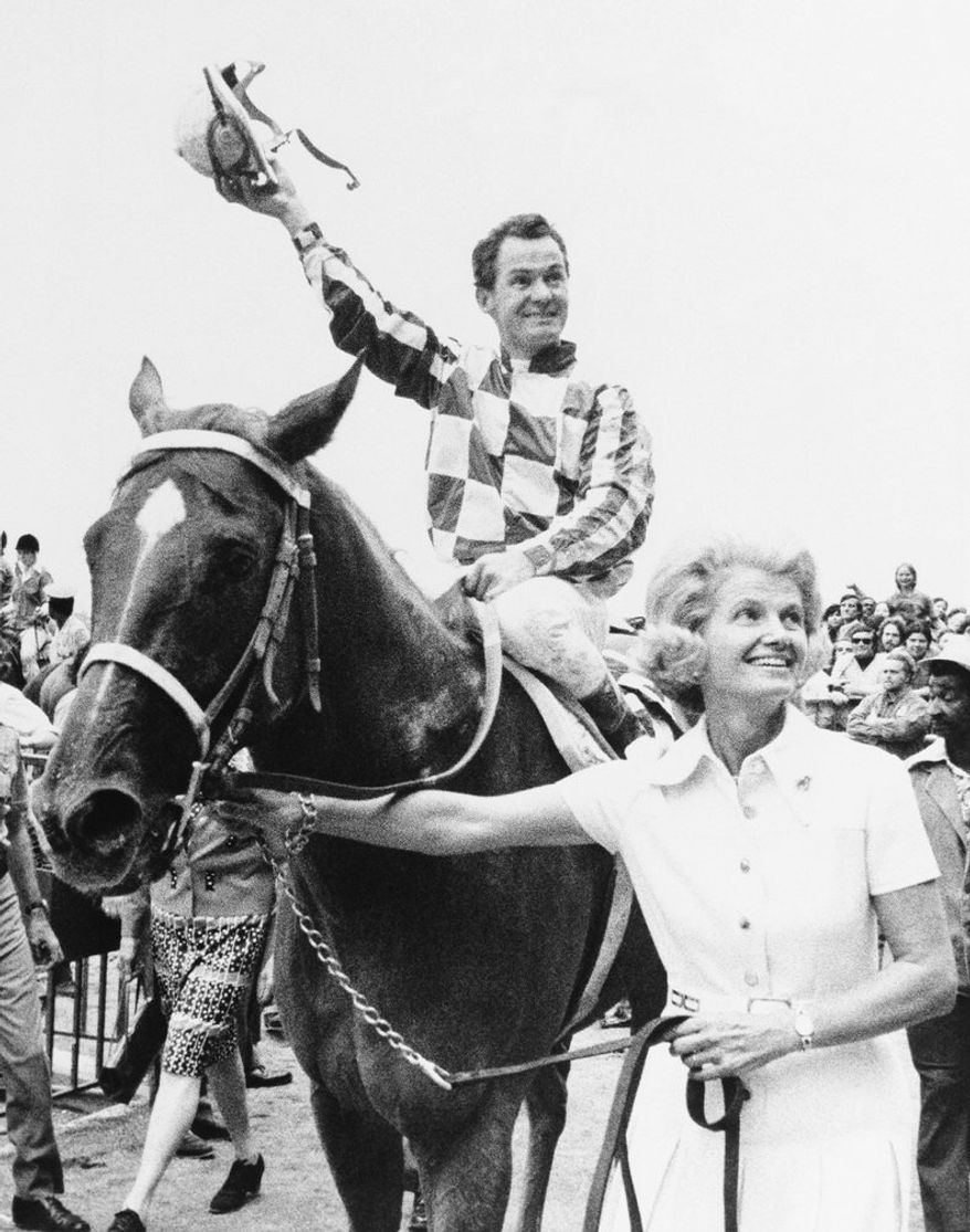 Penny Chenery leads Secretariat to the Winner's Circle at Belmont racetrack in Elmont, New York , Sept. 15, 1973, after he won the $250,000 Marlboro Cup Race. Jockey Ron Turcotte tips his hat to the race fans. (AP Photo)