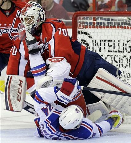 Washington Capitals goalie Braden Holtby (70) takes a skate in the face from New York Rangers right wing Ryan Callahan (24) in the second period of Game 5 first-round NHL Stanley Cup playoff hockey series, Friday, May 10, 2013, in Washington. (AP Photo/Alex Brandon)