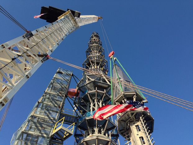 The silver spire topping One World Trade Center is fully installed on the building's roof, bringing the structure to its full, symbolic height of 1,776 feet on Friday, May 10, 2013, in New York. The 408-foot spire, weighing 758 tons, will serve as a world-class broadcast antenna. (AP Photo/Mark Lennihan)