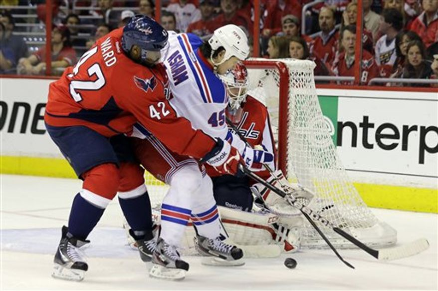 Washington Capitals right wing Joel Ward (42) guards New York Rangers right wing Arron Asham (45) as he works in front of goalie Braden Holtby (70) in the third period of Game 5 first-round NHL Stanley Cup playoff hockey series, Friday, May 10, 2013, in Washington. (AP Photo/Alex Brandon)