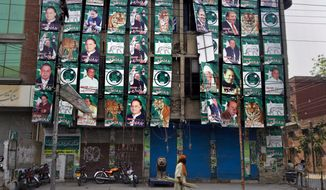 A Pakistani man walks past posters of former Prime Minister Nawaz Sharif, the Pakistan Muslim League-N party chief, on display on the party's office building in Lahore, Pakistan, on Sunday, May 12, 2013. (AP Photo/Anjum Naveed)