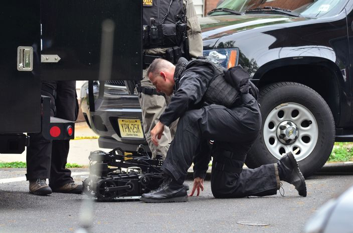 A New Jersey State Police swat team member readies a robot to enter a home in which a man had barricaded himself on Friday, May 10, 2013, in Trenton, N.J. (AP Photo/The Trentonian, Scott Ketterer)