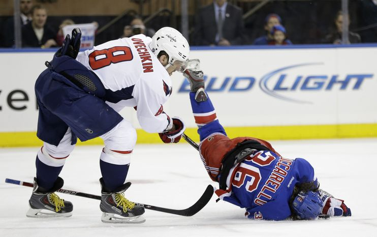 New York Rangers right wing Mats Zuccarello (36), of Norway, flips and hits the puck with his head in front of Washington Capitals left wing Alex Ovechkin (8), of Russia, in the second period of Game 6 of their NHL Stanley Cup hockey playoff series in New York, Sunday, May 12, 2013. (AP Photo/Kathy Willens)