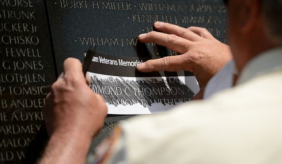 A volunteer with the Vietnam Veterans Memorial makes a rubbing of Spc. Raymond Clark Thompson for his wife Patty Thompson of West Palm Beach, Fla., Washington, D.C., Sunday, May 12, 2013. Patty attended a Mother's Day ceremony to honor Raymond and three other American servicemen who have been added to the wall. (Andrew Harnik/The Washington Times)