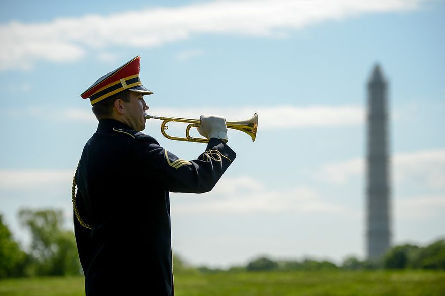 A member of the U.S. Army Band plays taps at a Mother's Day ceremony to honor four American servicemen who have been added to the wall of the Vietnam Veterans Memorial, Washington, D.C., Sunday, May 12, 2013. (Andrew Harnik/The Washington Times)