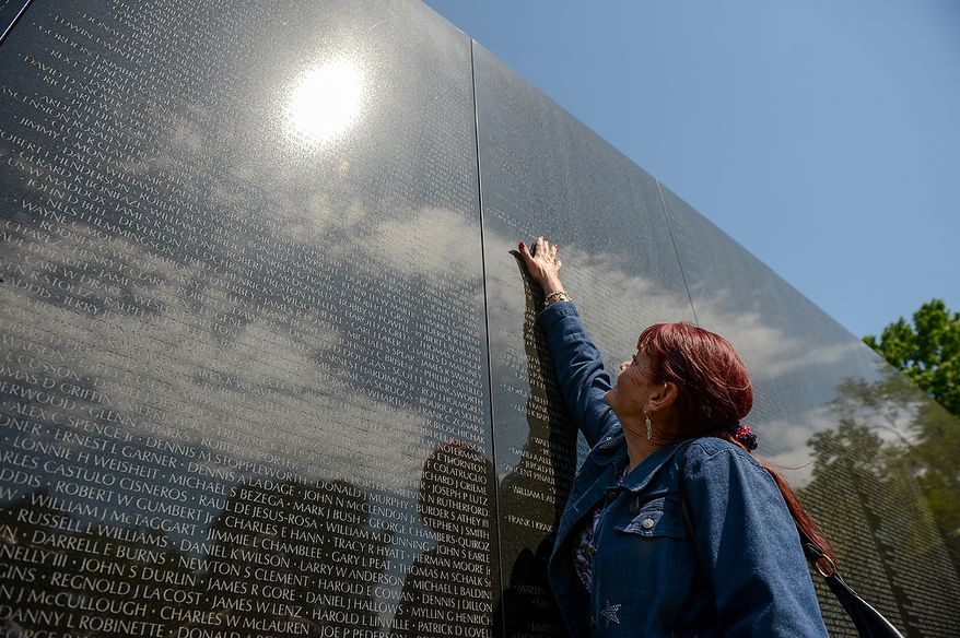 Patty Thompson of West Palm Beach, Fla., reaches up to touch the name of her husband, Spc. Raymond Clark Thompson who has been added to the wall of the Vietnam Veterans Memorial following a Mother's Day ceremony to honor Raymond and three other American servicemen who have been added to the wall, Washington, D.C., Sunday, May 12, 2013. (Andrew Harnik/The Washington Times)