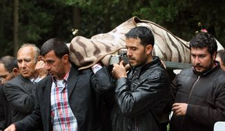 Pallbearers carry the remains of Fehmi Karaca, 69, a shop owner who was killed in Saturday's explosions, for burial in Reyhanli, near Turkey's border with Syria, on Sunday, May 12, 2013. The bombings marked the biggest incident of cross-border violence since the start of Syria's bloody civil war and have raised fears of Turkey's being pulled deeper into the conflict. (AP Photo/Burhan Ozbilici)