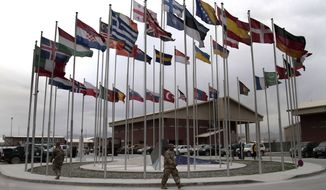 NATO soldiers walk under country-member flags at a NATO base at Kabul International Airport in Kabul, Afghanistan, on Tuesday, April 30, 2013. (AP Photo/Rahmat Gul)