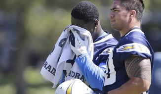 San Diego Chargers Manti Te'o takes a break as teammate Melvin Ingram wipes away the sweat during the hot weather during the teams' OTA's in San Diego, Monday, May 13, 2013. (AP Photo/Lenny Ignelzi)