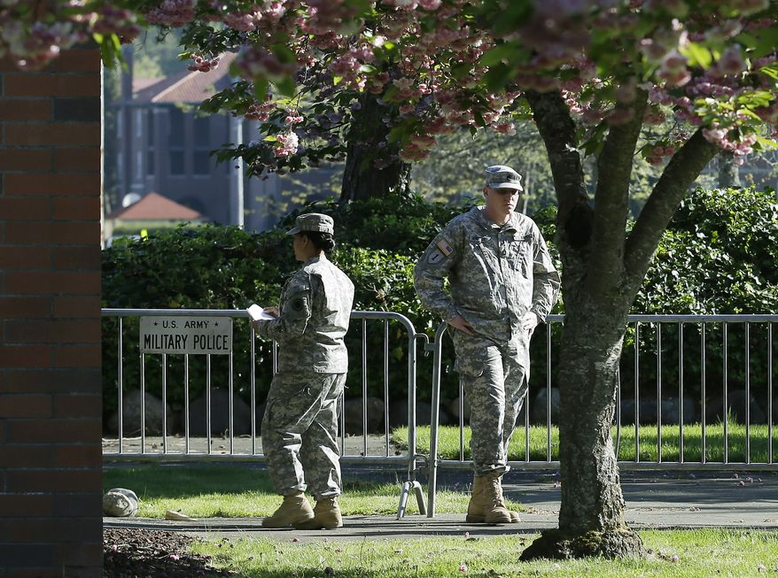 Soldiers assist with communications and security tasks outside the building at Joint Base Lewis-McChord in Washington state where the court-martial of U.S. Army Sgt. John Russell was taking place on Monday, May 6, 2013. (AP Photo/Ted S. Warren)