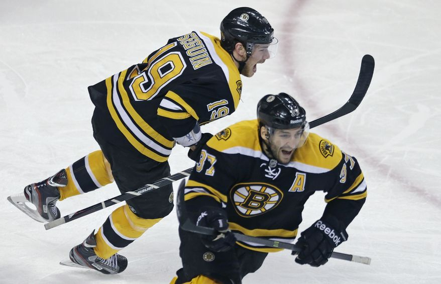 Boston Bruins center Patrice Bergeron (37) and teammate Nathan Horton, rear, celebrate after beating the Toronto Maple Leafs during overtime in Game 7 of their NHL hockey Stanley Cup playoff series in Boston, Monday, May 13, 2013. Bergeron scored the game-winning goal as the Bruins won 5-4. (AP Photo/Charles Krupa)