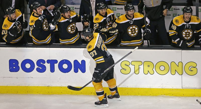 Boston Bruins center Patrice Bergeron (37) is congratulated by teammates after his goal in the final minute of the third period, which tied the game 4-4 forcing overtime against the Toronto Maple Leafs, in Game 7 of their NHL hockey Stanley Cup playoff series in Boston, Monday, May 13, 2013. (AP Photo/Charles Krupa)