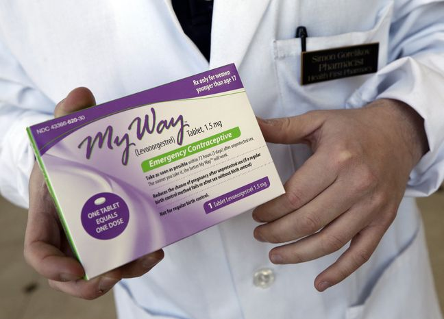 **FILE** Pharmacist Simon Gorelikov holds a generic emergency contraceptive at the Health First Pharmacy in Boston on May 2, 2013. (Associated Press)
