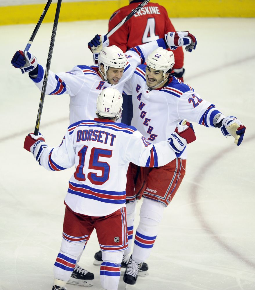 New York Rangers left wing Taylor Pyatt (14) celebrates his goal with Derek Dorsett (15) and Brian Boyle (22) during the second period of Game 7 first-round NHL Stanley Cup playoff hockey series against the Washington Capitals, Monday, May 13, 2013, in Washington. (AP Photo/Nick Wass)