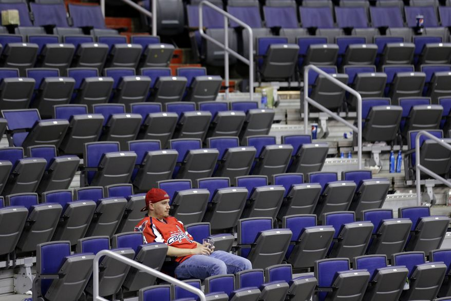 A Washington Capitals fan sits in the stands after Game 7 first-round NHL Stanley Cup playoff hockey series against the New York Rangers, Monday, May 13, 2013 at Verizon Center in Washington. The Rangers won 5-0. (AP Photo/Alex Brandon)