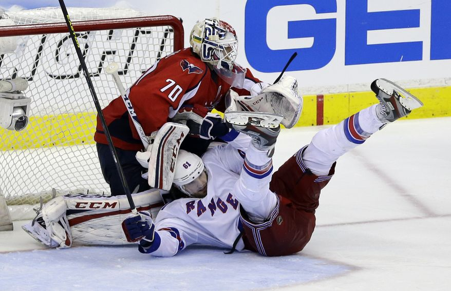 New York Rangers left wing Rick Nash (61) slides into Washington Capitals goalie Braden Holtby (70) in overtime of Game 5 first-round NHL Stanley Cup playoff hockey series, Friday, May 10, 2013 in Washington. The Capitals won 2-1, in overtime. (AP Photo/Alex Brandon)
