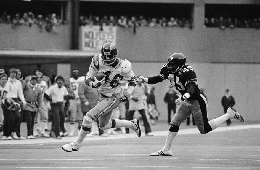 **FILE** San Diego Chargers Chuck Muncie breaks free from Pittsburgh Steelers defender Dwayne Woodruff as he runs for a gain during fourth quarter NFL action in Pittsburgh on Sunday, Jan. 9, 1983. Muncie ran for 126-yards in the game to help lead his team to a 31-28 win in the NFL playoff game. (AP Photo/Rusty Kennedy)