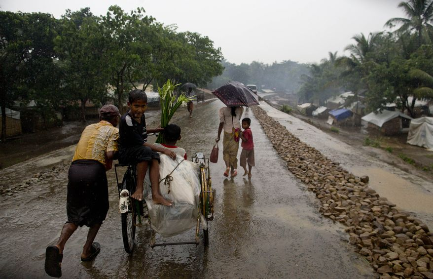 ** FILE ** An internally displaced Rohingya man pushes a rickshaw past makeshift tents at a camp for Rohingya people in Sittwe in Myanmar's northwestern Rakhine state on Tuesday, May 14, 2013, ahead of the arrival of Cyclone Mahasen, expected later this week. (AP Photo/Gemunu Amarasinghe)