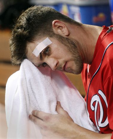 **FILE** Washington Nationals' Bryce Harper wipes his face in the dugout during the fourth inning of a baseball game against the Cincinnati Reds, Saturday, May 12, 2012, in Cincinnati. Harper cut his forehead Friday night breaking a bat off the field. (AP Photo/Al Behrman)